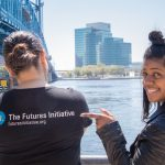 Two people, one wearing Futures Initiative t-shirt, the other pointing to logo and smiling