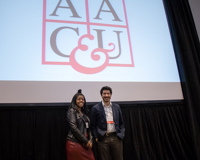 Mike Rifino and Lauren Melendez in front of AAC&U logo