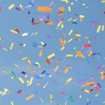 Multicolored confetti against blue sky