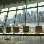 Photo of empty chairs in front of window withNYC skyline
