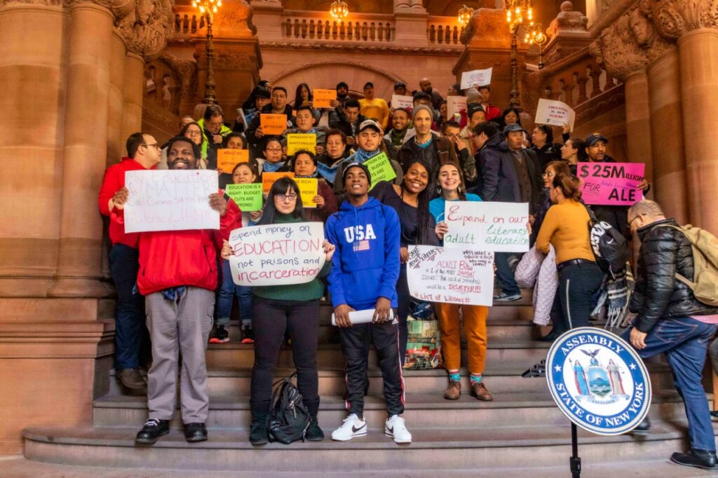 Image of students & educators holding sign advocating for an increase in literacy funding for the NY State budget.